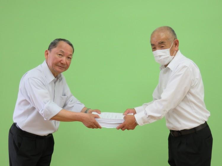 千葉土建の山田氏(右)から署名を受け取る住民の会の吉田氏=25日、木更津市
